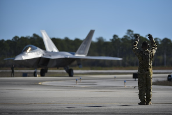 An F-22 Raptor assigned to the 95th Fighter Squadron, Tyndall Air Force Base, Fla., is marshalled in by a forward area refueling point Air Commando with the 1st Special Operations Logistic Readiness Squadron at Hurlburt Field, Fla., Feb. 26, 2017. FARP Airmen refueled three F-22s from an MC-130J Commando II tanker aircraft assigned to the 9th Special Operations Squadron, Cannon AFB, N.M., during the operation. The F-22 Raptor is the Air Force's newest fighter aircraft, combining stealth, supercruise, maneuverability and integrated avionics. (U.S. Air Force photo by Airman 1st Class Joseph Pick)