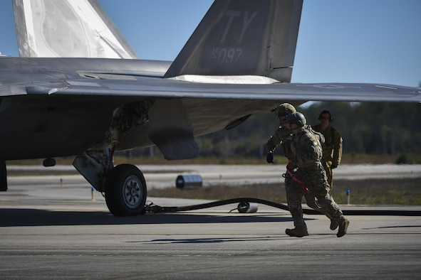 Forward area refueling point Air Commandos with the 1st Special Operations Logistic Readiness Squadron sprint around an F-22 Raptor during a FARP operation at Hurlburt Field, Fla., Feb. 26, 2017. FARP Airmen refueled three F-22s from an MC-130J Commando II assigned to the 9th Special Operations Squadron, Cannon AFB, N.M. (U.S. Air Force photo by Airman 1st Class Joseph Pick)