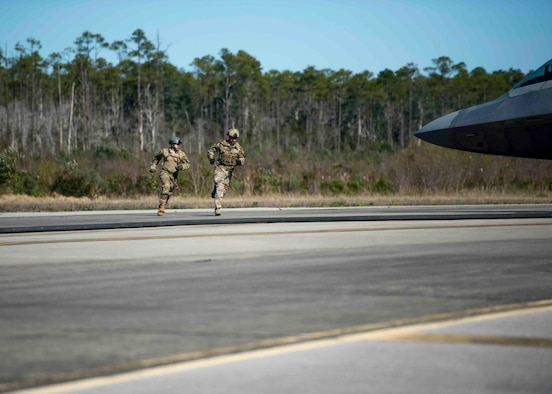 Forward area refueling point Airmen with the 1st Special Operations Logistic Readiness Squadron sprint around an F-22 Raptor during a FARP operation at Hurlburt Field, Fla., Feb. 26, 2017. FARP Airmen refueled three F-22s from an MC-130J Commando II tanker aircraft assigned to the 9th Special Operations Squadron, Cannon AFB, N.M. (U.S. Air Force photo by Senior Airman Krystal Garrett)