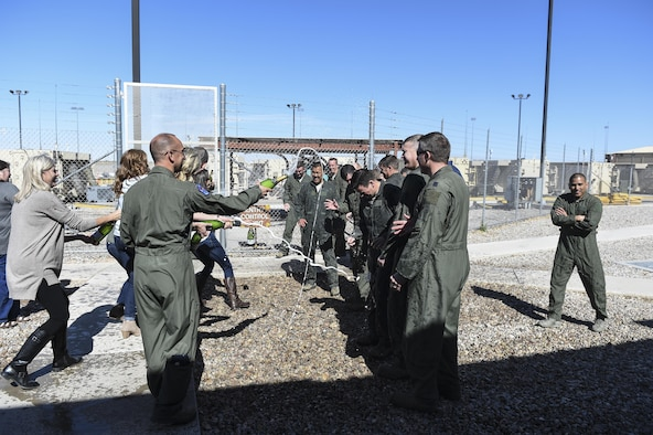 Aircrew for the MQ-1 Predator are sprayed down with water and champagne after the MQ-1's final flight Feb. 27, 2017 at Holloman Air Force N.M. The MQ-1 Predator has provided many years of service and is being phased out of service as the Air Force transitions to the more capable MQ-9 Reaper. The MQ-1 Predator is an armed, multi-mission, medium-altitude, long-endurance remotely piloted aircraft that is employed primarily as an intelligence-collection asset and secondarily against dynamic execution targets.  (U.S. Air Force Photo by Staff Sgt. Stacy Jonsgaard)