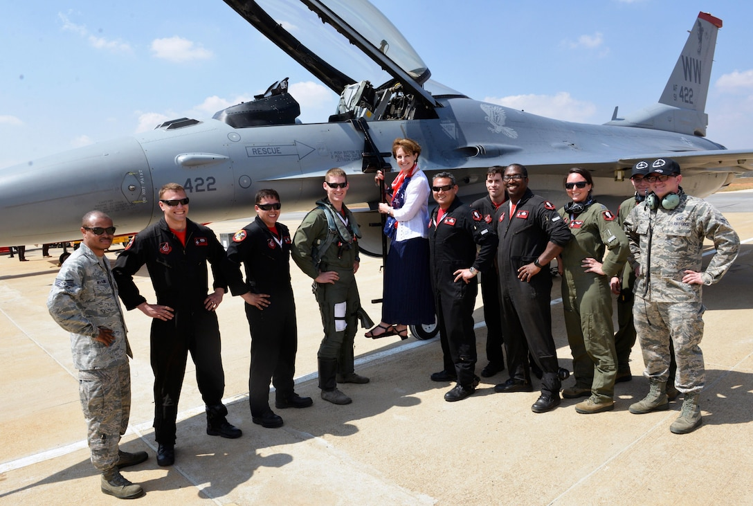 The U.S. Air Force's Pacific Air Forces Demonstration Team members pose for a photo with MaryKay Carlson, Charge d'Affaire for U.S. Mission to India during opening day events for Aero India 2017 at Air Force Station Yelahanka Feb. 16, 2017. The F-16 Fighting Falcon is a compact, multi-role fighter aircraft. It is highly maneuverable and has proven itself in air-to-air combat and air-to-surface attack and provides a relatively low-cost, high-performance weapon system for the United States and allied nations. The United States participates in air shows and other regional events to demonstrate its commitment to the security of the Indo-Asia-Pacific region, promote the standardization and interoperability of equipment, and display capabilities critical to the success of current and future military operations. (U.S. Air Force photo by Capt. Mark Lazane)