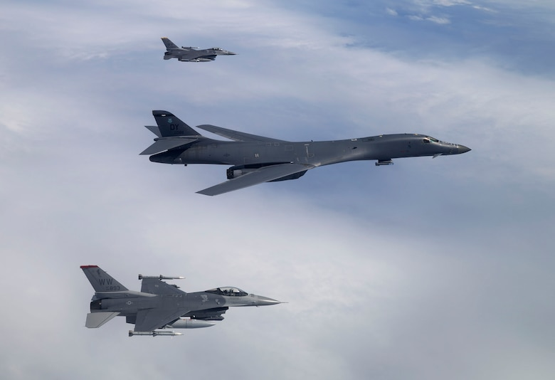 Two F-16 Fighting Falcons escort a B-1B Lancer during COPE NORTH 17, Feb. 13, 2017. The Falcons provided the Lancers with tactical escort as they strike targets on air interdiction training sorties, all while suppressing enemy air defenses while the Lancers drop bombs on training targets. (Courtesy photo by Jim Haseltine)