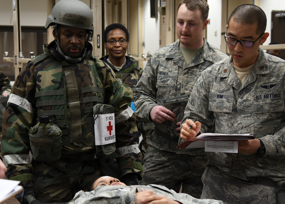 "U.S. Air Force Staff Sgt. Richard Johns, left, 51st Medical Operations Squadron physical therapy technician, Senior Airman John Cody, middle, 51st MDOS medical technician, and Maj. Nathan Kim, right, 51st MDOS physician, treat a simulated patient during Exercise Beverly Herd 17-1 at Osan Air Base, Republic of Korea, Feb. 28, 2017.  Exercise Beverly Herd 17-1 offered a multitude of scenarios for Team Osan medics to practice, helping ensure their ability to ""Fight Tonight."" (U.S. Air Force photo by Airman 1st Class Gwendalyn Smith)"