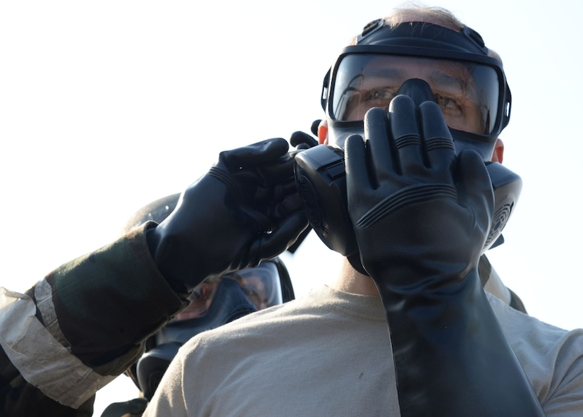 U.S. Air Force Staff Sgt. Nicolette Sanchez, left, with 51st Bioenvironmental, helps Senior Airman Luke Markle, 51st Munitions Armament, with doffing his gas mask during Exercise Beverly Herd 17-1 at Osan Air Base, Republic of Korea, Feb. 28, 2017. The first time being held, civil engineer and medical personnel tested the effectiveness of the chemical contaminant avoidance area, which was designed to quickly process large amounts of individuals through decontamination in a safe zone. (U.S. Air Force photo by Tech. Sgt. Ashley Tyler)