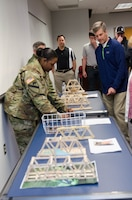 TAM Deputy Commander LTC Taneha Carter and DPPM Tom Waters look over the submissions for the competition before the judging starts, marking National Engineers Week, Feb. 24.