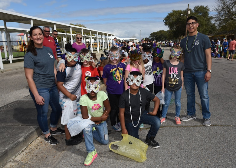 Airman Gabrielle Wychoff, 81st Security Forces Squadron administrator, and Airman 1st Class Eric Martinez, 81st SFS entry controller, pose for a photo with students at Jeff Davis Elementary School during its Mardi Gras Parade, Feb. 24, 2017, Biloxi, Miss. The Keesler AFB Honor Guard and other base personnel also participated in the festivities. (U.S. Air Force photo by Kemberly Groue)