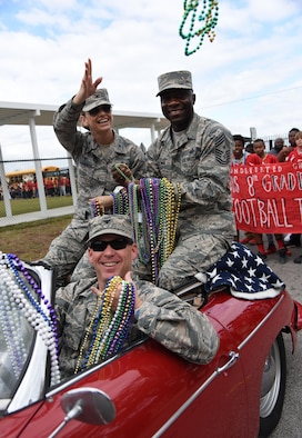 Col. C. Mike Smith, 81st Training Wing vice commander, drives Col. Michele Edmondson, 81st TRW commander, and Chief Master Sgt. Vegas Clark, 81st TRW command chief, as they serve as Grand Marshals during the Jeff Davis Elementary School Mardi Gras Parade, Feb. 24, 2017, Biloxi, Miss. The Keesler AFB Honor Guard and other base personnel also participated in the festivities. (U.S. Air Force photo by Kemberly Groue)
