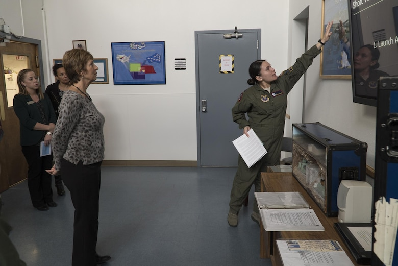 Capt. Kirsten McKenzie, 90th Operations Group missile procedural trainer instructor, describes the launch sequence of a Minuteman III intercontinental ballistic missile to Laura Hyten, wife of Gen. John E. Hyten, U.S. Strategic Command commander, during a site visit to F.E. Warren Air Force Base, Wyo., Feb. 22, 2017. The MPT ensures missileers are proficient at their tasks and duties while pulling alerts in the missile field. Mrs. Hyten toured the base to meet with Airmen and families of the Mighty Ninety. (U.S. Air Force Photo by Lan Kim)