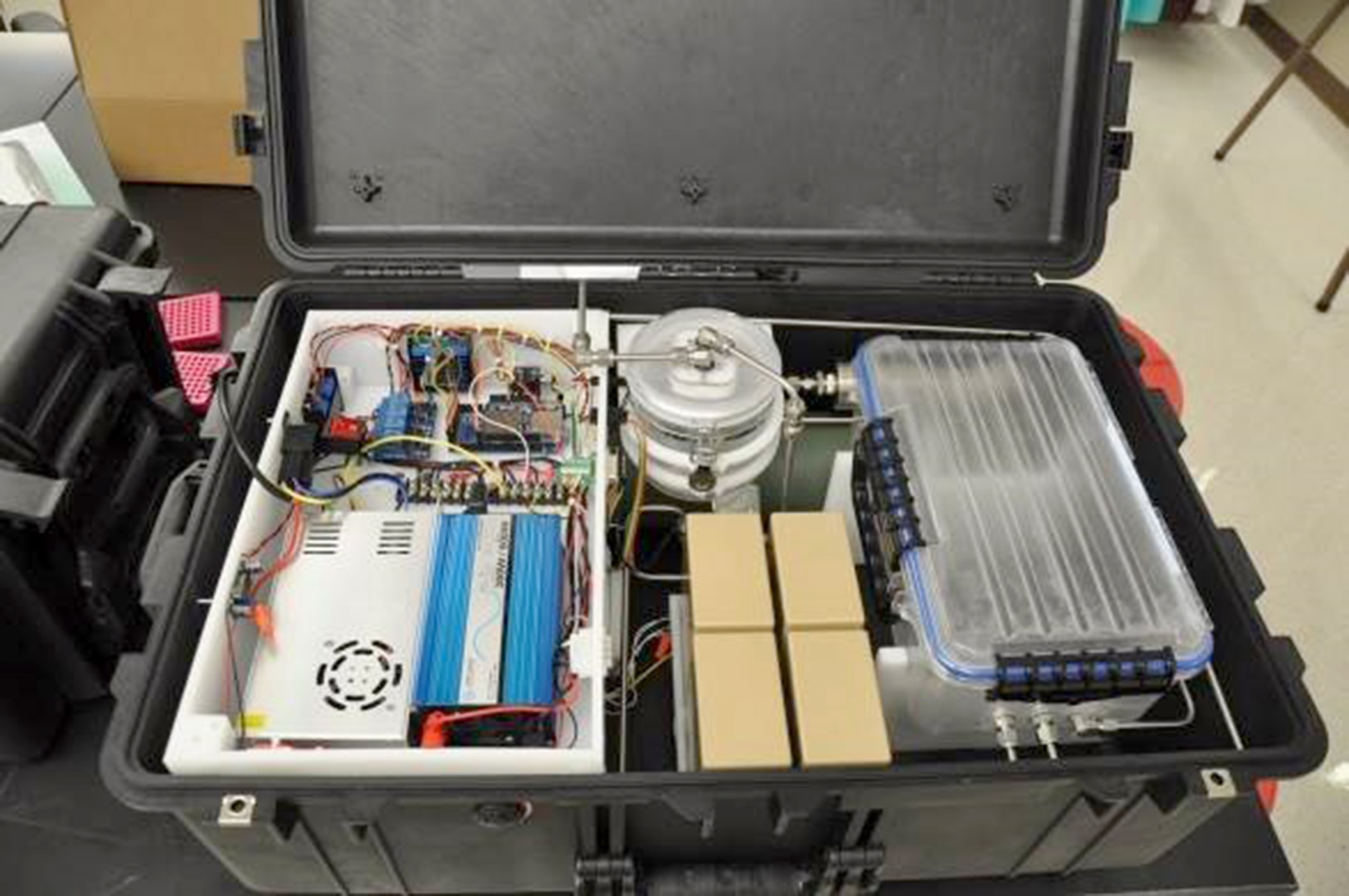 The Naval Medical Research Unit San Antonio-redesigned field portable ozone sterilizer chamber is housed in a ruggedized case and can be powered by rechargeable batteries or an external power source.