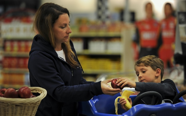 Master Sgt. Jodi Zellers, a contracting officer with the Air Force Test Center at Eglin Air Force Base, hands her son an apple at Hurlburt Field, Fla., Feb. 22, 2017. The Health and Wellness Center staff held an event at the commissary to teach the community habits for a heart-healthy life in recognition of National Heart Health Month. (U.S. Air Force photo by Airman 1st Class Dennis Spain)