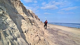 """Thomas Laczo, hydraulic engineer for the U.S. Army Corps of Engineers, Baltimore District, assesses impacts on a sand dune in Ocean City, Maryland, as part of a team conducting post-storm damage assessments of the Atlantic Coast of Maryland Shoreline Protection Project Jan.27, 2016 after a powerful winter storm nicknamed """"Winter Storm Jonas."""" The dune and beach berm in front of it provide a buffer to help reduce the impacts of coastal storms on homes and infrastructure behind the berm and dune system."""