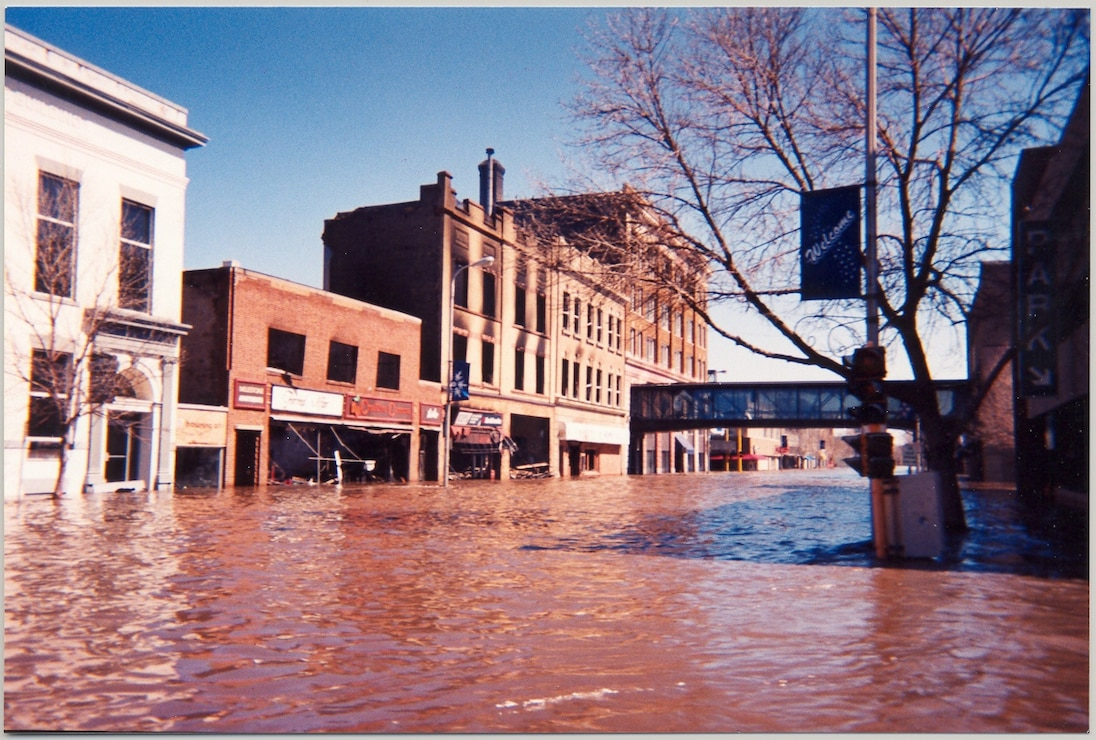 Floodwaters inundate 4th Street N., downtown Grand Forks, N.D., April 25, 1987. The photo is looking towards Demers Avenue. The second, third and fourth buildings on the left hand side were torn down after the flood.  --USACE St. Paul District file photo