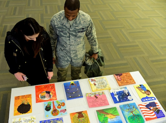 Samantha Clark and her husband Senior Airman Jason Clark, a unit deployment manager assigned to the 28th Communications Squadron, view art during the African American Heritage Month celebration inside the Deployment Center at Ellsworth Air Force Base, S.D., Feb. 28, 2017. The event showcased art submitted from Airmen, high school students and children from the Child Development Center. (U.S. Air Force photo by Airman 1st Class Randahl J. Jenson)