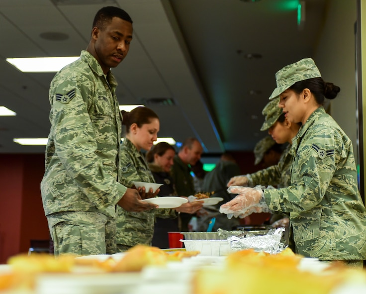 Airmen shuffle through a line, filling their plates with food during the African American Heritage Month celebration inside the Deployment Center at Ellsworth Air Force Base, S.D., Feb. 28, 2017. Shrimp jambalaya, grits and beans were just some of the kinds of food served. (U.S. Air Force photo by Airman 1st Class Randahl J. Jenson)