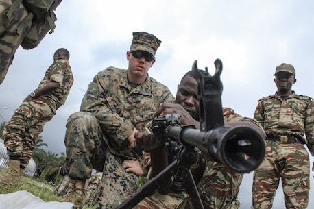 Lance Cpl. Jordan Adams, a rifleman with Special Purpose Marine Air-Ground Task Force Crisis Response-Africa, watches as soldiers with the Cameroonian Naval Commando Company demonstrates weapons handling techniques in Limbé, Cameroon, Nov. 16, 2016.  Marines trained together with the COPALCO in small unit tactics, weapons handling, first aid treatment and leadership skills during their time together.  (U.S. Marine Corps photo by Cpl. Alexander Mitchell/released)