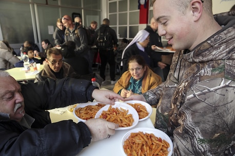 Navy RPSN Alexander Varner, a religious program specialist with Special Purpose Marine Air-Ground Task Force Crisis Response-Africa, hands out plates of pasta at a soup kitchen in Catania, Italy, Dec. 29, 2016.  Marines and sailors volunteered their time to help clean up the area and serve food during the holiday season.  (U.S. Marine Corps photo by Cpl. Alexander Mitchell/released)