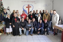 Marines and sailors with Special Purpose Marine Air-Ground Task Force Crisis Response-Africa, stand for a group photo with workers at a soup kitchen in Catania, Italy, Dec. 29, 2016.  Marines and sailors volunteered their time to help clean up the area and serve food during the holiday season.  (U.S. Marine Corps photo by Cpl. Alexander Mitchell/released)