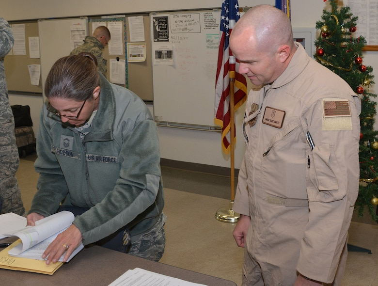 Senior Master Sgt. Durk Smith, a medical flight technician assigned to the 465th Air Refueling Squadron has his deployment orders reviewed prior to deploying by Senior Master Sgt. Julie Hudson, 507th Logistics Readiness Squadron distribution flight superintendent at Tinker Air Force Base, Oklahoma, December 12, 2016. (This image was blurred for operational security/U.S. Air Force Photo/Tech. Sgt. Lauren Gleason)