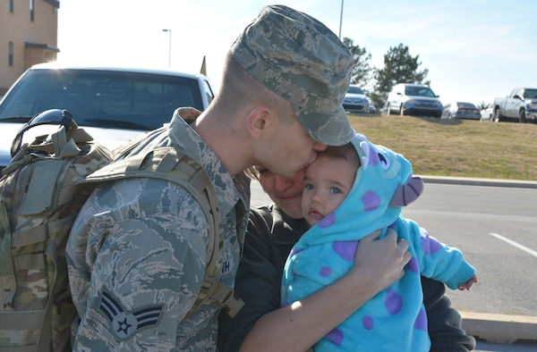 Senior Airman Harlan Smith, 507th Aircraft Maintenance Squadron kisses his daughter and embraces his girlfriend prior to departing for a deployment to Incirlik Air Base, Turkey. Smith joined 93 other Citizen Airmen from the 507th Air Refueling Wing at Tinker Air Force Base, Oklahoma who deployed prior to the holiday December 13, 2016.  (U.S. Air Force Photo/Maj. Jon Quinlan)