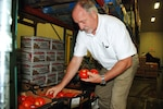DLA Troop Support's Ken Wilmoth, who leads one of six garrison feeding teams that carry out the DoD Fresh Fruit and Vegetable Program, inspects tomatoes destined for elementary schools at the prime vendor's location in Greensboro, North Carolina.
