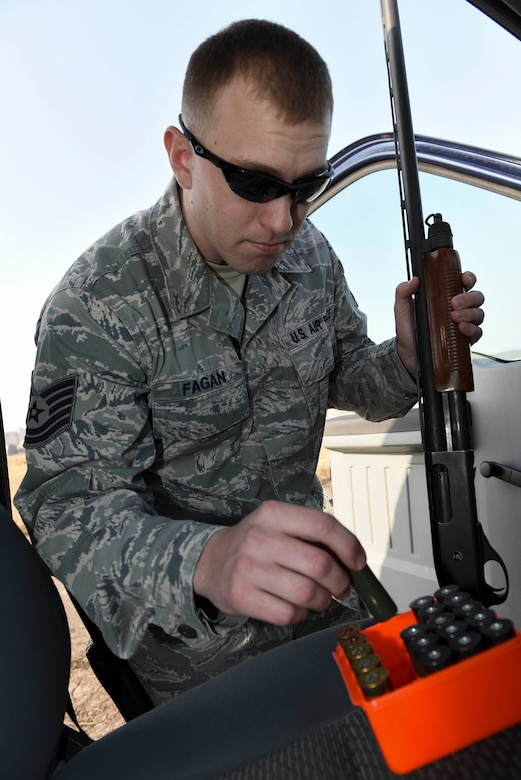 Tech. Sgt. Blake Fagan, 8th Operations Support Squadron aircraft management training noncommissioned officer in charge, picks up ammunition for his shotgun at Kunsan Air Base, Republic of Korea, Jan. 3, 2017. Fagan uses multiple tools as part of the Bird/wildlife Aircraft Striking Hazard program to deter wildlife that could cause significant damage to aircraft. (U.S. Air Force photo by Senior Airman Michael Hunsaker)