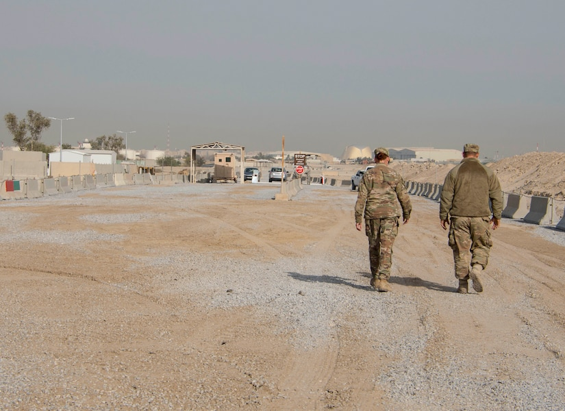 Tech. Sgt. Lora Ramos, left, and Senior Airman William Klein, right, of the 557th RED HORSE walk down a newly built road at an undisclosed location in Southwest Asia Dec. 30, 2016. The 387th Air Expeditionary Group enlisted the help of various squadrons and groups to complete the new road and entry control point in approximately four months. (U.S. Air Force photo/Senior Airman Andrew Park)