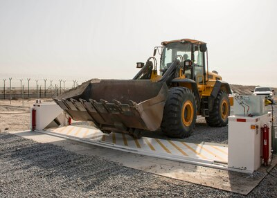 Staff Sgt. Phillip Smith of the 557th RED HORSE drives a front-end loader over a barricade at the new entry control point at an undisclosed location in Southwest Asia Dec. 30, 2016. RED HORSE assisted the 387th Expeditionary Support Squadron civil engineering flight with portions of the road project requiring heavy equipment. (U.S. Air Force photo/Senior Airman Andrew Park)