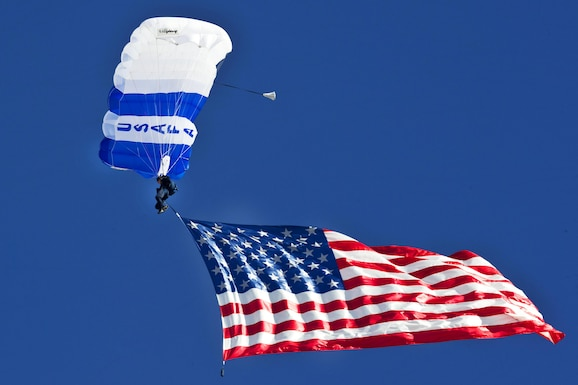 A U.S. Air Force Academy cadet from the Wings of Blue demonstration team displays the U.S. Flag midair. (U.S. Air Force photo/Airman 1st Class Jason Couillard)