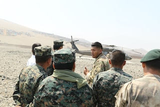 A U.S. Army medic with Special Operations Command South explains helicopter evacuation operations to Peruvian counterparts May 2, 2016, in Ancon, Peru during Fuerzas Comando 2016. Sgt. Christian Ortiz from San Diego, CA, helped organize medical processes and procedures with Peruvian first responders and Kentucky National Guard UH-60 Black Hawk crew members. (U.S. Army photo by Cpl. Joanna Bradshaw/Released)