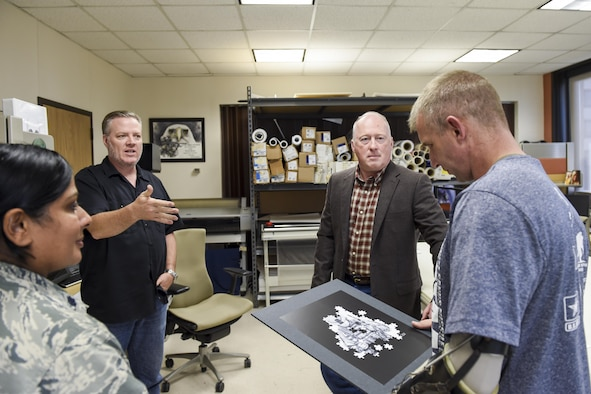 Retired Master Sgt. William Vance, 59th Medical Wing graphics illustrator, presents one of his famous artworks, the Post-Traumatic Stress Disorder art piece, to Lt. Col. Kenneth Dwyer, patient and Special Forces officer assigned to the U.S. Army 1st Special Forces Command (Airborne), at Wilford Hall Ambulatory Surgical Center on Joint Base San Antonio-Lackland, Texas, Nov. 18, 2016. The PTSD art piece has been reproduced and seen all over the world and is currently part of the Pentagon's Air Force Art Program. (U.S. Air Force photo/Staff Sgt. Michael Ellis)