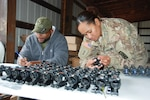 Shannon Woodyard from DLA Distribution New Cumberland, Pennsylvania, helps a 10th Mountain Division supply sergeant turn in excess optical sighting devices at Fort Drum, New York.