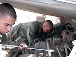 Army Pfc. Guillermo Armendariz and Pfc. James Vail change an engine in a Bradley fighting vehicle in Hit, Iraq. The transmission of the Bradley is a critical part the DLA Warstopper Program makes sure is available.