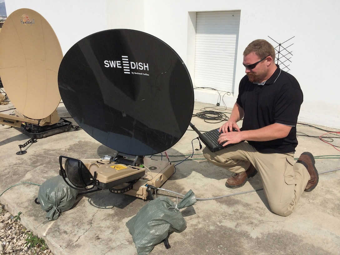 Mark Bossen, a contingency information technology specialist in DLA Information Operations, sets up the system relied on by members of JTF Matthew to communicate between the base location and field sites, as well as DLA Headquarters.