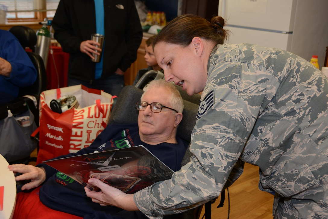 Tech. Sgt. Stephanie Heath, 507th Mission Support Group administrative assistant, shows a Veteran one of his Christmas gifts during the annual Norman Veterans Center Christmas Party at the Norman Veterans Center in Norman, Okla., Dec. 22, 2016. This year marked the 21st year that the 507th Air Refueling Wing has participated in the annual Christmas party at the center. (U.S. Air Force photo/Maj. Jon Quinlan)