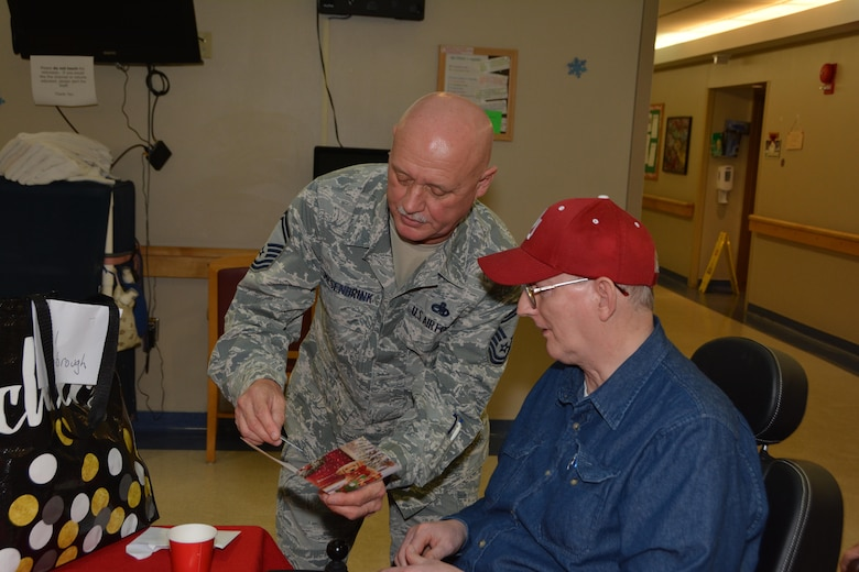 Senior Master Sgt. Rodney Mesenbrink of the 507th Maintenance Squadron presents a gift card to a resident of the Norman Veterans Center Dec. 22, 2016 in Norman, Okla.  Approximately 35 Airmen from Tinker Air Force Base visited and delivered gifts to the Veterans.(U.S. Air Force photo/Maj. Jon Quinlan)