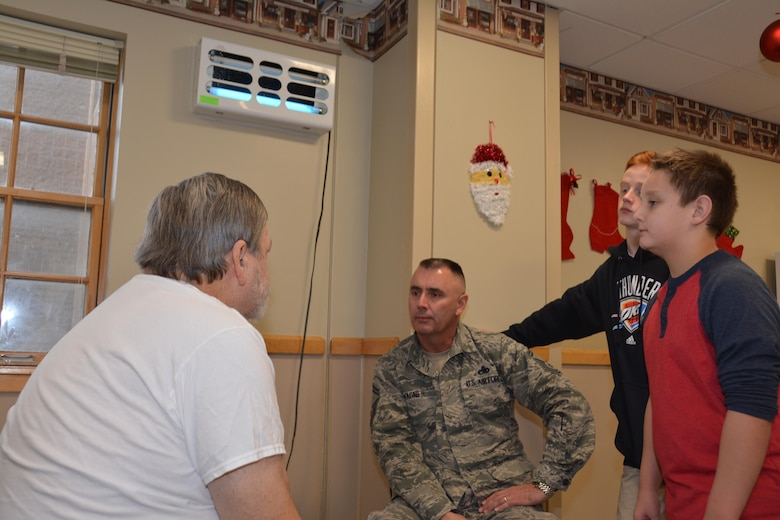 Master Sgt. Jon Russell of the 507th Maintenance Squadron delivers a gift bag and listens to Norman Veterans Center resident talk about his time in the U.S. Army Dec. 22, 2016 in Norman, Okla. (U.S. Air Force photo/Maj. Jon Quinlan)