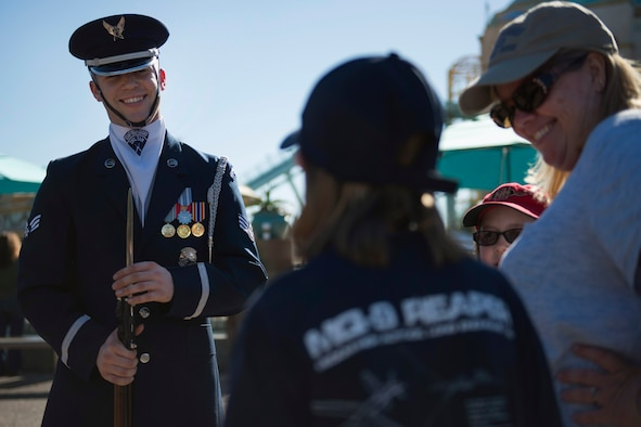 Senior Airman Jacob Wilson, U.S. Air Force Honor Guard Drill Team member, speaks with a young girl about the Air Force after a performance at Sea World in San Diego, Calif., Dec. 29, 2016. The drill team showcases their drill performances at public venues, such as Sea World, to recruit and inspire the public. (U.S. Air Force photo by Senior Airman Philip Bryant)
