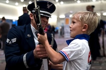 Senior Airman Angelo Hightower, U.S. Air Force Honor Guard Drill Team member, lets a young boy hold a drill rifle at the Live on Green event in Pasadena, Calif., Dec. 30, 2016. The M-1 Garand rifles weigh approximately 12 pounds and have dull bayonets attached at their tips. (U.S. Air Force photo by Senior Airman Philip Bryant)