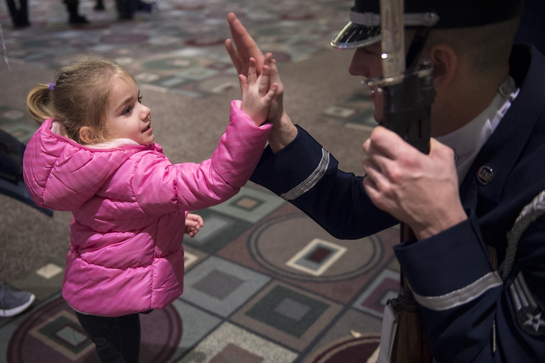 Senior Airman Joshua Blanton, U.S. Air Force Honor Guard Drill Team member, high-fives a young girl at the Live on Green event in Pasadena, Calif., Dec. 30, 2016. The drill team took time after each performance to take photos, answer questions and interact with crowd members. (U.S. Air Force photo by Senior Airman Philip Bryant)