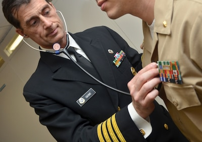 Navy Capt. Jesse Geibe, Naval Hospital Jacksonville director for public health, listens to a patient's heart rate. The Jacksonville Business Journal honored Geibe as a 2016 Health Care Hero. Defense Department officials are reminding military and civilian employees that they must report their health care coverage to the Internal Revenue Service when they file their 2016 federal income tax form. Navy photo by Jacob Sippel