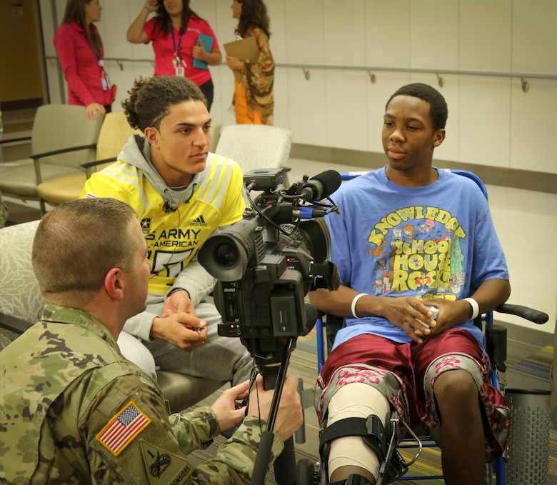 Army Reserve Staff Sgt. Steve Engle, a broadcast journalist with the 367th Mobile Public Affairs Detachment, 318th Press Camp Headquarters, interviews 15-year-old Jalen Williams (right), one of the children in the Children's Health Department of the University Hospital in San Antonio Jan. 3, as Jaelan Phillips (left) a high-school student and defensive end for the west team of the U.S. Army All-American Bowl looks on.  More than 30 high-school athletes participating in the upcoming Army All-American Bowl and their Soldier mentors took the opportunity to visit with kids at the hospital as part of a community relations event.  For 16 years the Army All-American Bowl has been the nation's premier high school football game, serving as the preeminent launching pad for America's future college and National Football League stars. (Official U.S. Army Reserve Photo by Sgt. 1st Class Brent C. Powell)
