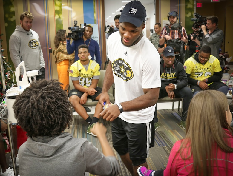 Cam Akers, a running back from Clinton, Mississippi, who will represent the east team in the Army All-American Bowl on Jan. 7, gives a fist bump to Brian McGraw, one of the children in the Children's Heath Department of the University Hospital in San Antonio.  More than 30 athletes and their Soldier mentors took the opportunity to visit with kids at the hospital as part of a community relations event Jan. 3.  For 16 years the Army All-American Bowl has been the nation's premier high school football game, serving as the preeminent launching pad for America's future college and National Football League stars. (Official U.S. Army Reserve Photo by Sgt. 1st Class Brent C. Powell)