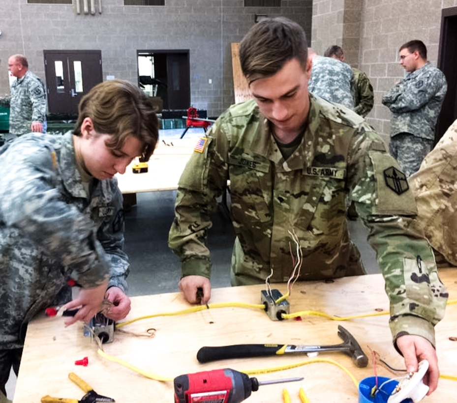 Pfc. Gabrielle F. Coppedge, left, and Spc. Steph Jones, right, work together to wire a three-way switch that controls a lighting system at the 672nd Engineer Company vertical engineer skills competition held Dec. 10 in Missoula, Mont. The vertical engineer skills competition was held to inspire the same enthusiasm for vertical engineers that is held in other areas of the Corps of Engineers, and to show off Army Reserve life to members of the community (U.S. Army Reserve Photo by Sgt. 1st Class Leroy E. Bierfreund/Released).