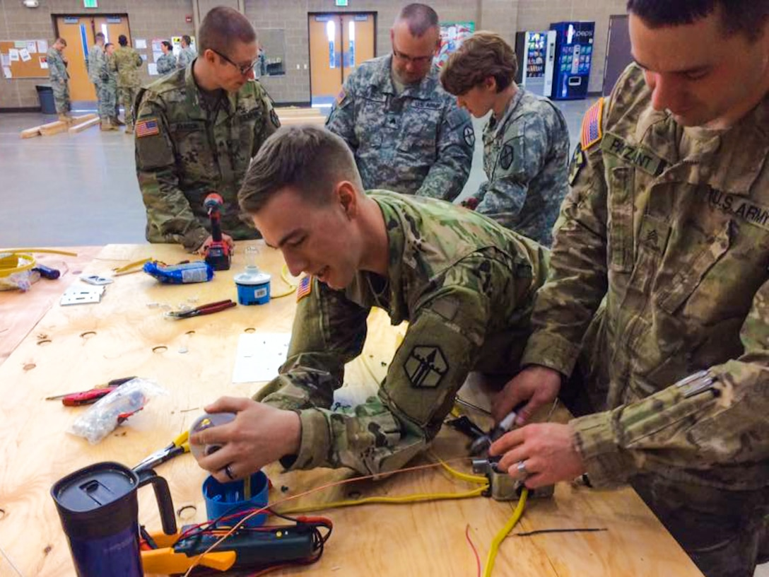 Sgt. Justin C. Payzant and Spc. Steph Jones put the finishing touches on wiring for a light and single pole switch at the 672nd Engineer Company vertical engineer skills competition held Dec. 10 in Missoula, Mont. The vertical engineer skills competition was held to inspire the same enthusiasm for vertical engineers that is held in other areas of the Corps of Engineers, and to show off Army Reserve life to members of the community (U.S. Army Reserve Photo by Sgt. 1st Class Leroy E. Bierfreund/Released).