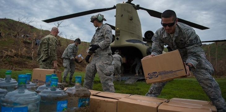 U.S. service members stack boxes of aid  which and water while off loading a U.S. Army CH-47 Chinook during an aid relief mission Oct. 14, 2016 in Anse d'Hainault, Haiti. Haiti was devastated by hurricane Matthew which killed more than 800 people. Joint Task Force Matthew is a comprised of multinational partners who are working together to provide and bring aid to those in need in Haiti.  (U.S. Air Force photo by Staff Sgt. Paul Labbe)