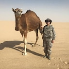 Cadet 1st Class Cinthya Elizondo-Gamez stands next to a camel during her Air Force Operations trip to Kuwait in 2016. (Courtesy photo)