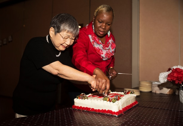 Hitomi Yamaguchi, a logistics-contractor specialist, left, Linda Brown, logistics contractor director, supervisor and friend to Yamaguchi, cut a retirement cake at Marine Air Station Iwakuni, Japan, Dec. 16, 2016. Yamaguchi celebrated her retirement after 42 years of service. She held four jobs in that time. She was a stock control clerk, voucher examiner, and an administrator specialist. However, she spent most of her time as a logistics-contractor specialist.  (U.S. Marine Corps photo by Lance Cpl. Gabriela Garcia-Herrera)