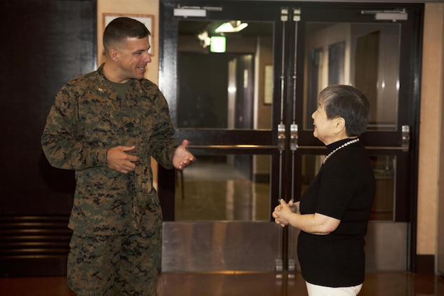 U.S. Marine Corps Lt. Col. Scott Stahl, director of contracting for Marine Corps Installaion Pacific, congratulates Hitomi Yamaguchi, a logistics-contractor specialist, on her retirement ceremony at Marine Corps Air Station Iwakuni, Japan, Dec. 16, 2016. Yamaguchi started working on the air station in 1974 and held four jobs during her 42 years of service as a stock control clerk, voucher examiner, and an administrator specialist.  However, she spent most of her time as a logistics-contractor specialist. (U.S. Marine Corps photo by Lance Cpl. Gabriela Garcia-Herrera)