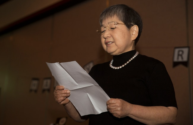 Hitomi Yamaguchi, a logistics-contractor specialist, reads a thank-you note she wrote to her guests during her retirement ceremony at Marine Corps Air Station Iwakuni, Japan, Dec. 16, 2016. Yamaguchi started working at the air station in 1974 and held four jobs during her 42 years of as a stock control clerk, a voucher examiner, and an administrator specialist. However, she spent most of her time as a logistics-contractor specialist. (U.S. Marine Corps photo by Lance Cpl. Gabriela Garcia-Herrera)