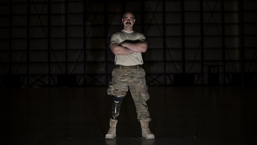Tech. Sgt. Jason Caswell, 455th Expeditionary Aircraft Maintenance Squadron C-130 Hercules debrief NCO-in-charge, stands in a C-130 hangar at Bagram Airfield, Afghanistan, Jan. 5, 2017. After a sports injury in 2010, Caswell underwent a year of surgeries, two years of painful limb-recovery therapy, followed by physical therapy. In October 2014, his limb still hadn't healed and began to worsen. Caswell elected to amputate his injured leg. (U.S. Air Force photo by Staff Sgt. Katherine Spessa)